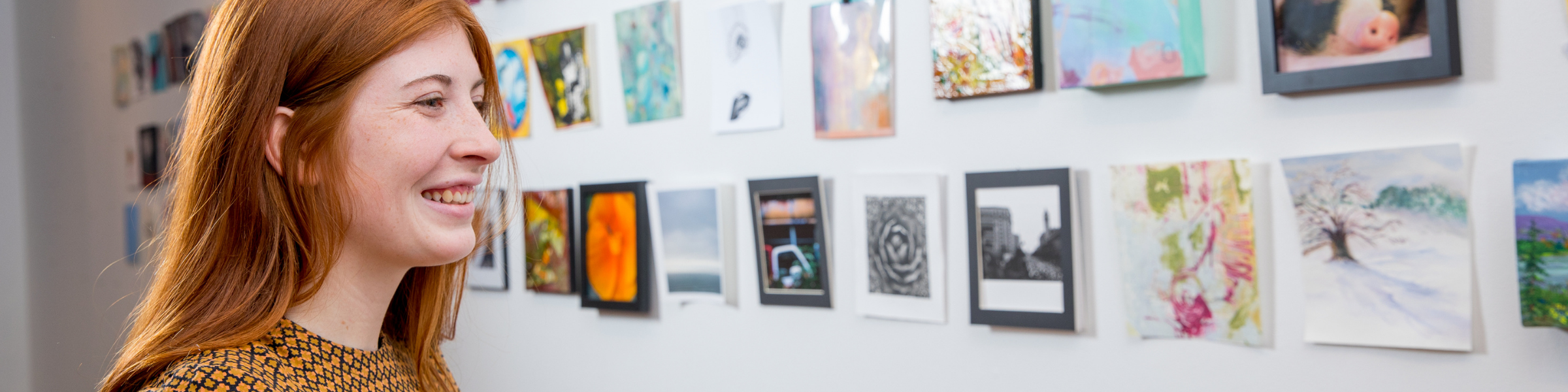 Woman looking at small paintings mounted on wall