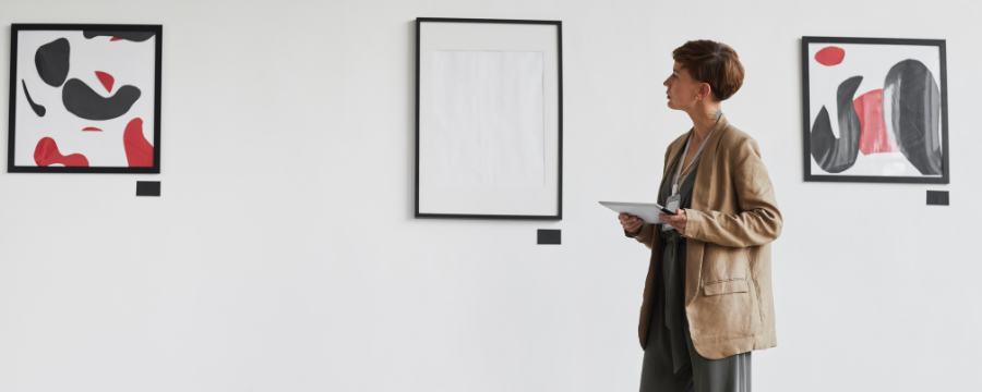 person in gallery space looking at abstract art on walls.