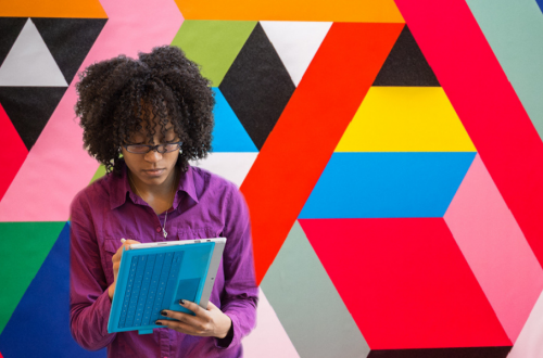 Student in front of colorful geometric backdrop with tablet