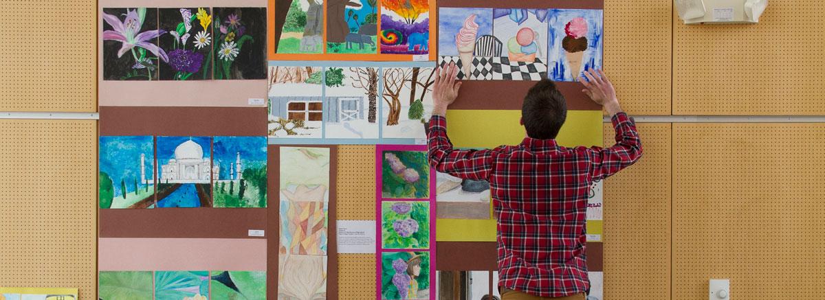 A teacher places elementary school artwork on a wall display.
