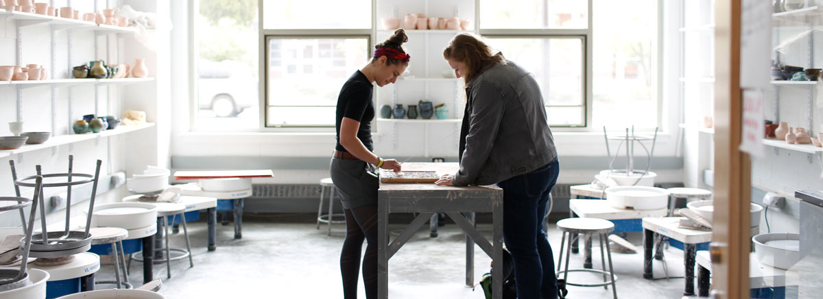 two students work in a ceramics studio.