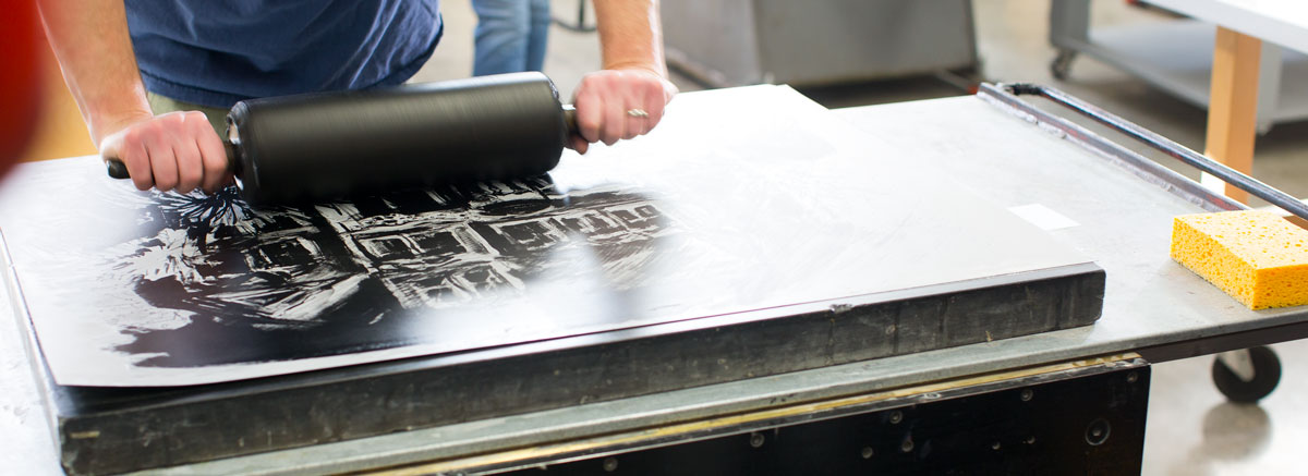 A student in the porcess of making a print.