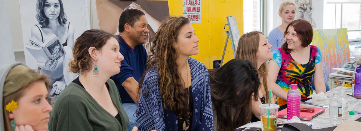 A group of students and a professor gather in a Studio Arts Building classroom.