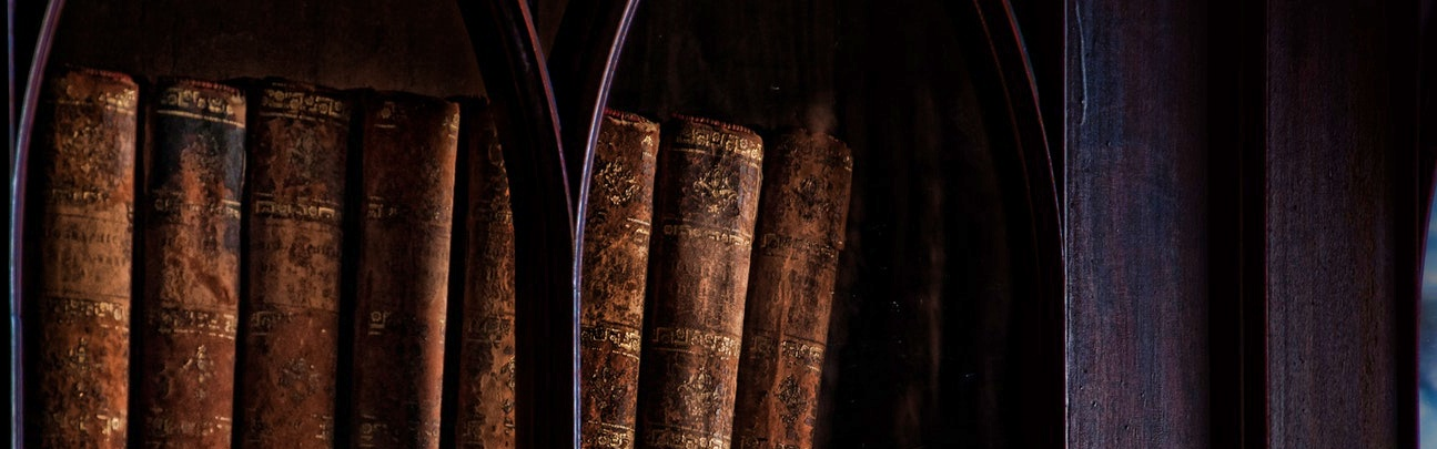 A dark-wood bookshelf holds eight rare books.