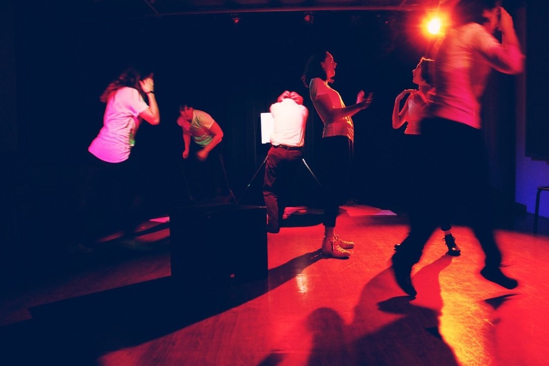 Student work image, actors moving in a red-lit space during a performance
